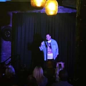 Logan Cummins performing stand-up comedy at Comedy at the Taproom